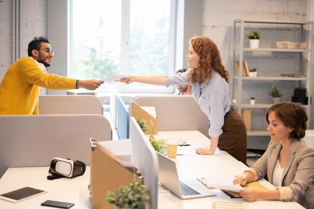 Grupo de especialistas jóvenes altamente calificados que trabajan en el departamento de seo: hombre hipster pasando documentos analíticos a un colega en la oficina