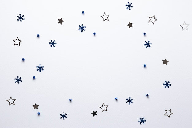 Grupo de estrellas y copos de nieve sobre fondo blanco.