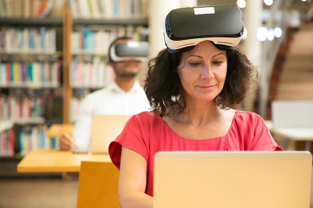 Grupo de estudiantes adultos que usan auriculares vr en clase de informática