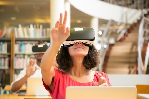 Grupo de estudiantes adultos que utilizan simuladores de realidad virtual para estudiar