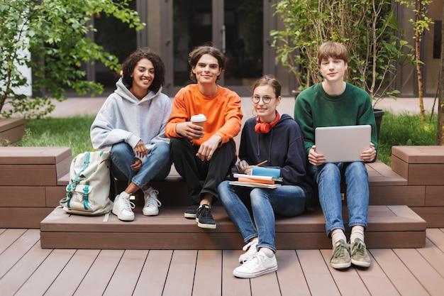 Grupo de estudiantes alegres y frescos sentados y felices pasar tiempo juntos en el patio de la universidad