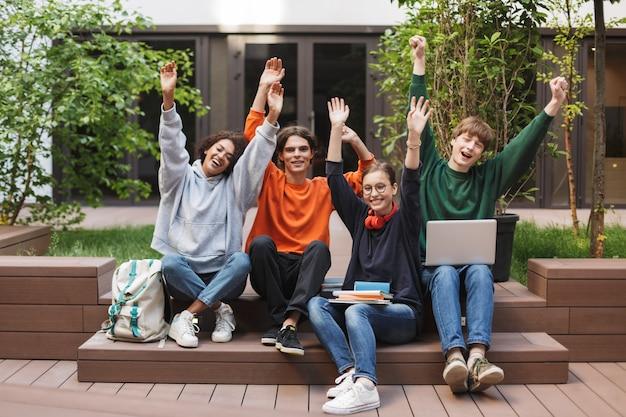 Grupo de estudiantes alegres sentados y levantando felizmente sus manos en el patio de la universidad