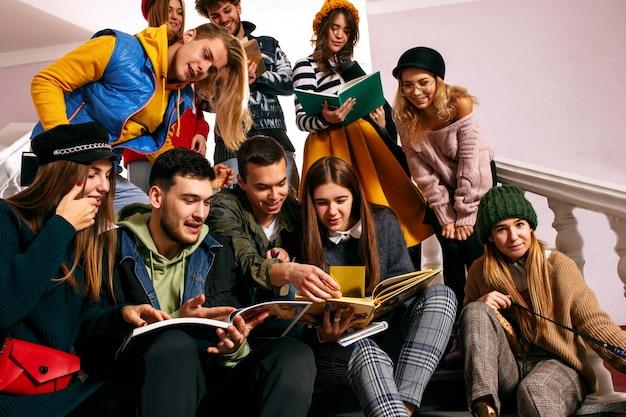 El grupo de estudiantes alegres sentados en una sala de conferencias antes de la lección.