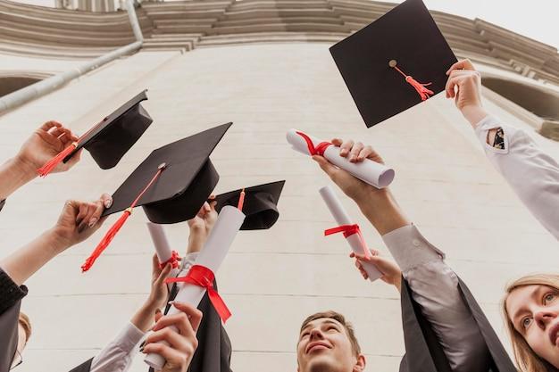 Grupo de estudiantes de ángulo bajo con diploma