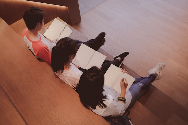 Grupo de estudiantes de asia sosteniendo cuadernos en blanco mientras está sentado en la biblioteca de la escalera con espacio de copia en tono vintage, educación y fondo del concepto de la gente