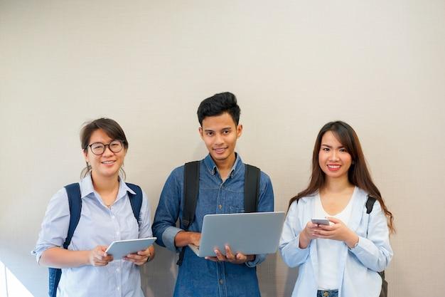 Grupo de estudiantes asiáticos con dispositivos electrónicos en el concepto de campus universitario