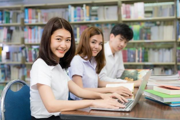Grupo de estudiantes asiáticos felices con computadora portátil