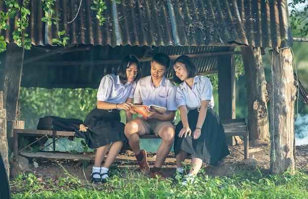 Grupo de estudiantes asiáticos en uniforme estudiando juntos al aire libre.