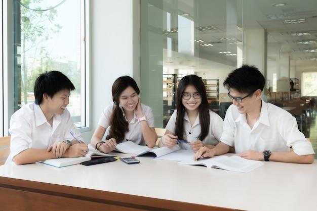 Grupo de estudiantes asiáticos en uniforme estudiando juntos en el aula.