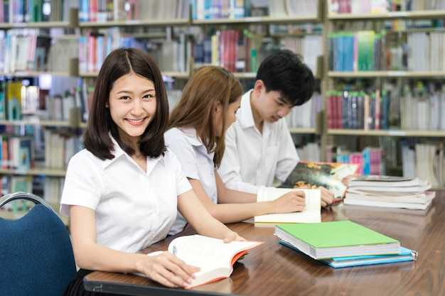 Grupo de estudiantes asiáticos en uniforme que estudian juntos en la biblioteca de la universidad.