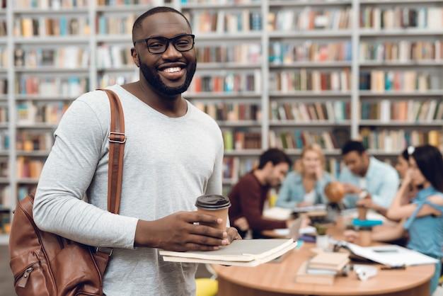 Grupo de estudiantes en biblioteca y chico negro con café.