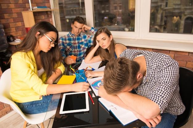 Grupo de estudiantes cansados trabajando duro juntos