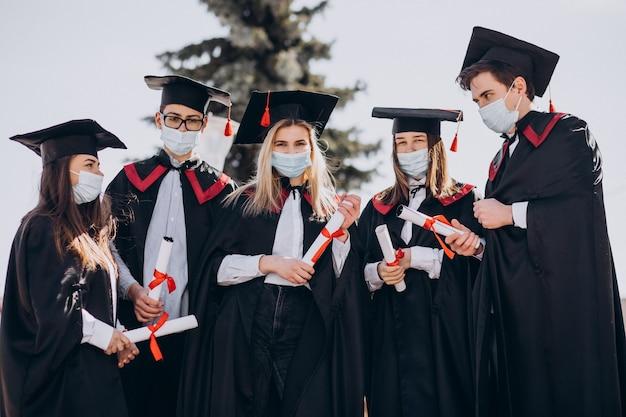 Grupo de estudiantes celebrando juntos la graduación y con máscaras faciales