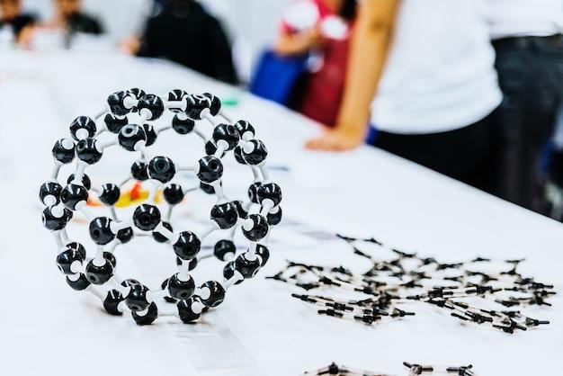 Grupo de estudiantes en clase de biología creando modelos moleculares con juguetes educativos.