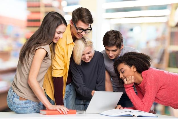 Grupo de estudiantes con computadora en la lección en el aula