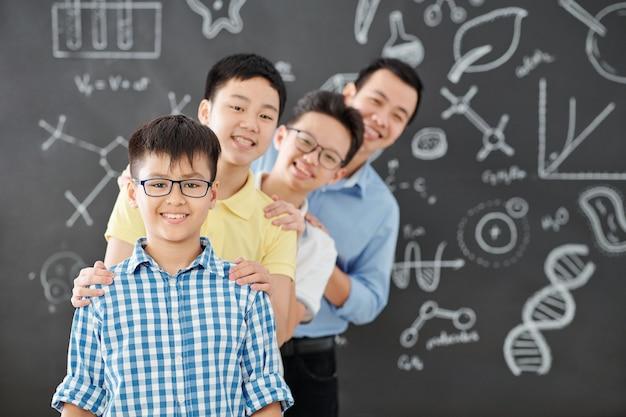 Grupo de estudiantes de la escuela vietnamita y su profesor de química de pie uno detrás del otro y sonriendo