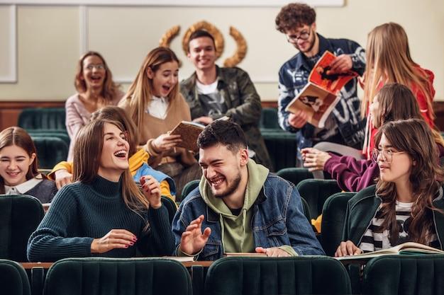 El grupo de estudiantes felices alegres sentados en una sala de conferencias antes de la lección