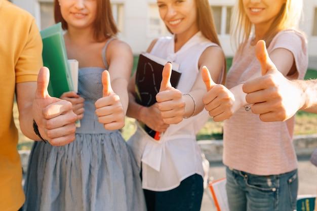 Grupo de estudiantes felices mostrando los pulgares para arriba primer plano