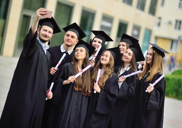 Un grupo de estudiantes graduados de maestría en túnicas negras o manto y sombreros cuadrados con diplomas en sus manos se toman selfies en la cámara de un teléfono inteligente ...