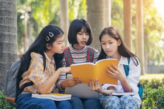 Grupo de estudiantes jóvenes y educación libro de lectura en el parque de la ciudad