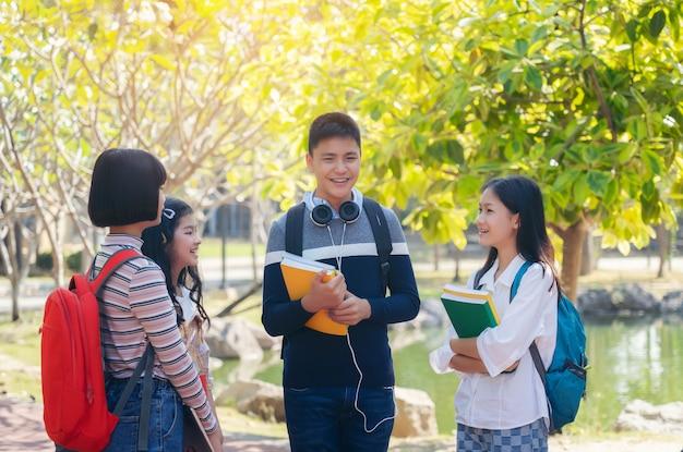 Grupo de estudiantes jóvenes felices caminando al aire libre, concepto de libro de estudiantes jóvenes diversos al aire libre