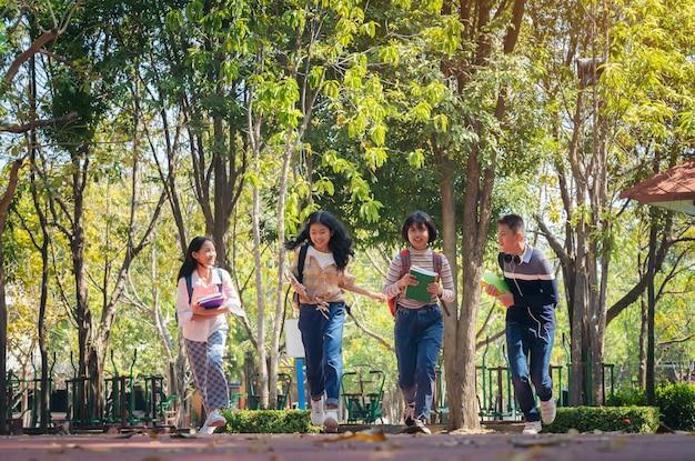 Grupo de estudiantes jóvenes felices corriendo al aire libre, concepto de libro de jóvenes estudiantes diversos al aire libre