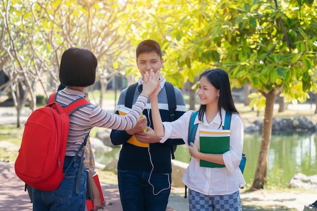 Grupo de estudiantes jóvenes felices tocan las manos al aire libre, concepto de libro de jóvenes estudiantes diversos al aire libre