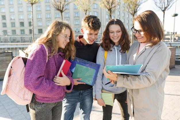 Grupo de estudiantes con maestra, adolescentes hablando con maestra