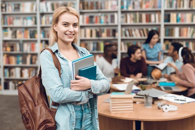 Grupo de estudiantes multiculturales étnicos sentado en la biblioteca.