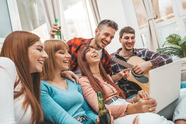 Grupo de estudiantes o adolescentes con computadoras laptop y tablet pc en casa divirtiéndose