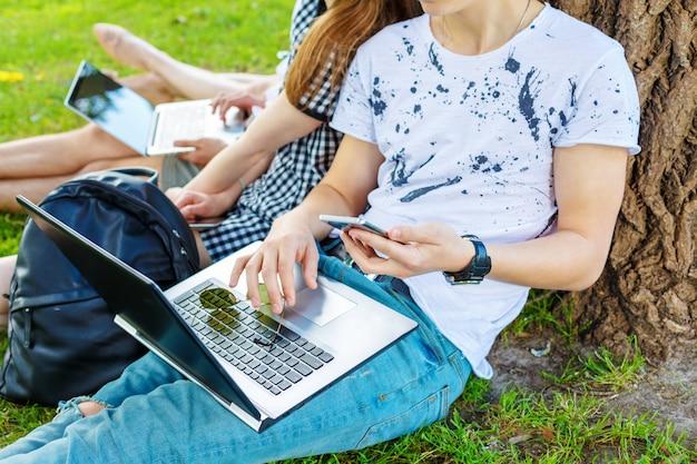 Grupo de estudiantes en un parque con computadoras portátiles abiertas sentados en el césped debajo de un árbol