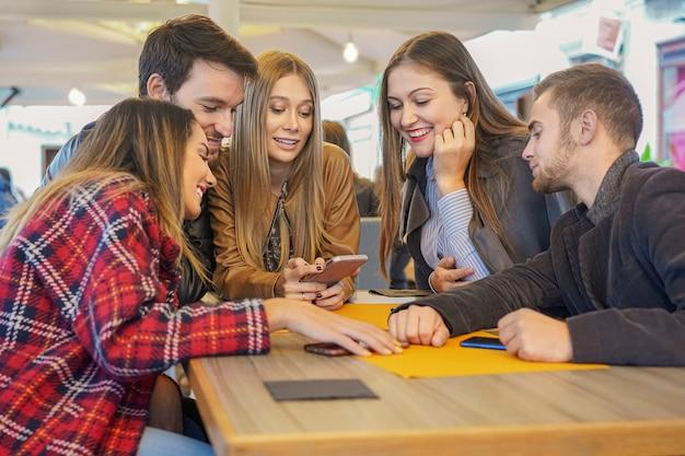 Grupo de estudiantes pasar el rato juntos sentados en un bar.