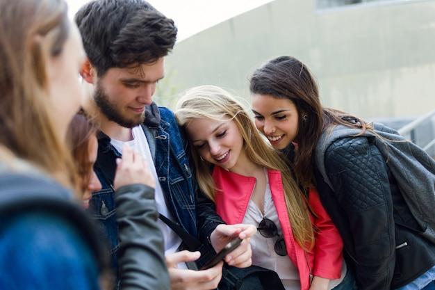 Un grupo de estudiantes que se divierten con smartphones después de clase.