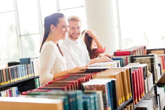 Grupo de estudiantes que estudian en la biblioteca y leyendo libros.