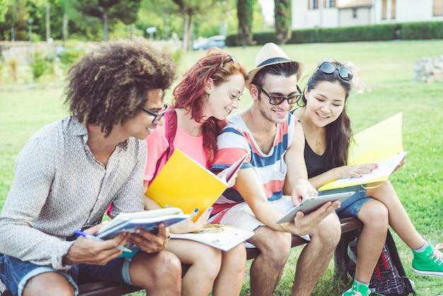 Grupo de estudiantes que estudian en el parque después de la escuela