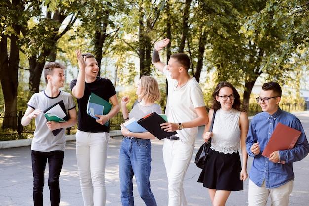 Grupo de estudiantes riendo con libros al aire libre en un parque de día soleado y edificio de la universidad