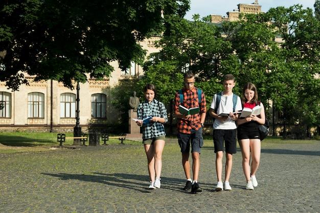 Grupo de estudiantes de secundaria leyendo mientras caminan