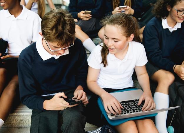 Grupo de estudiantes sentados en la escalera usando lptop