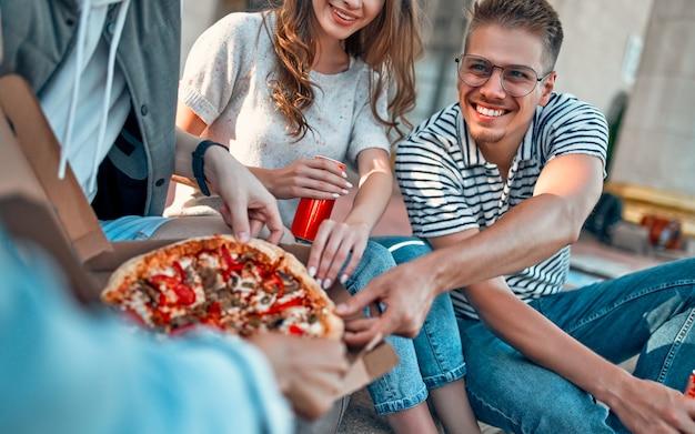 Un grupo de estudiantes se sienta en los escalones fuera del campus y comen pizza y refrescos.