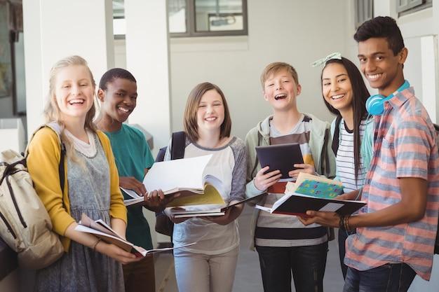 Grupo de estudiantes sonrientes de pie con el portátil en el pasillo