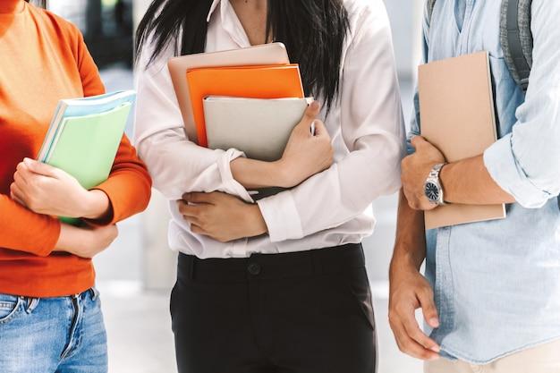 Grupo de estudiantes sosteniendo cuadernos al aire libre