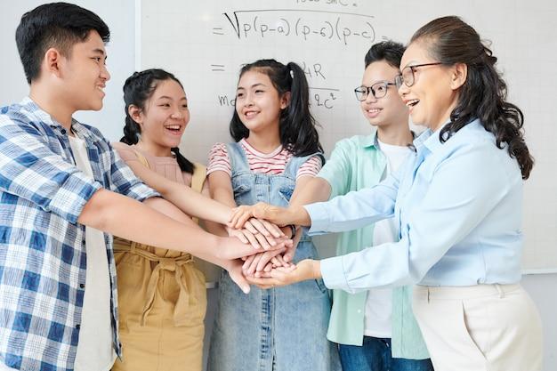 Grupo de estudiantes y su profesor de matemáticas apilando las manos para apoyarse mutuamente antes de la competencia de matemáticas