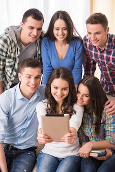 Grupo de estudiantes con tableta están haciendo foto selfie.