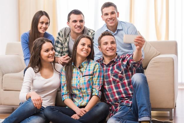 Grupo de estudiantes con teléfonos inteligentes están haciendo selfie.