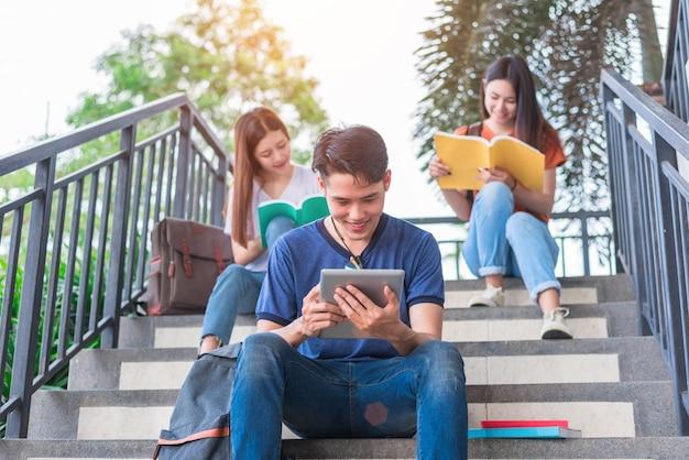 Grupo de estudiantes universitarios asiáticos que leen y que reparan por el libro de texto y la computadora portátil en la escalera en la universidad
