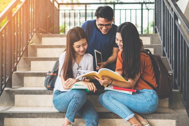 Grupo de estudiantes universitarios asiáticos usando tableta y teléfono móvil