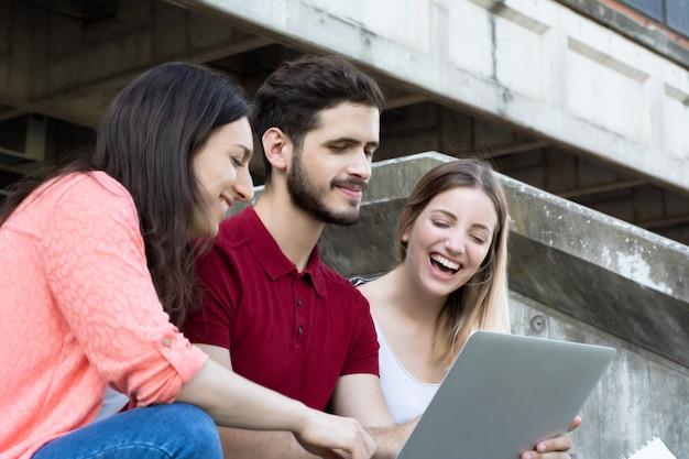 Grupo de estudiantes universitarios estudiando juntos al aire libre