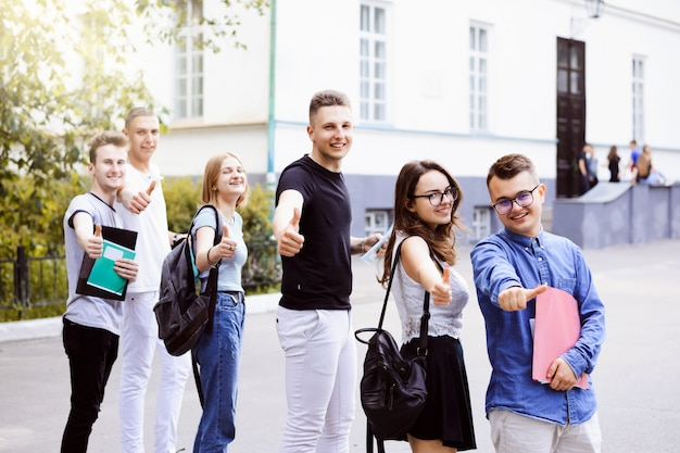 Grupo de estudiantes universitarios mostrando los pulgares para arriba