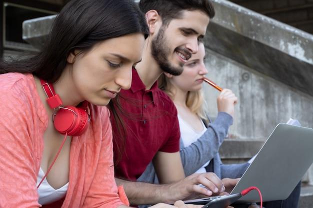 Grupo de estudiantes universitarios que estudian juntos al aire libre