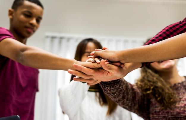 Grupo de estudio compañeros de clase uniéndose las manos.